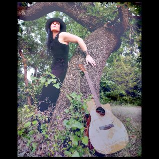 Musician/Vocalist Morgan standing against oak tree with guitar in foreground